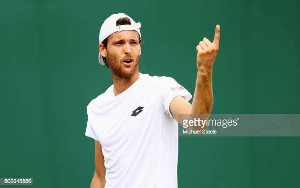 Joao Sousa of Portugal reacts during the Gentlemen's Singles first round match against Dustin Brown of Germany on day one of the Wimbledon Lawn...