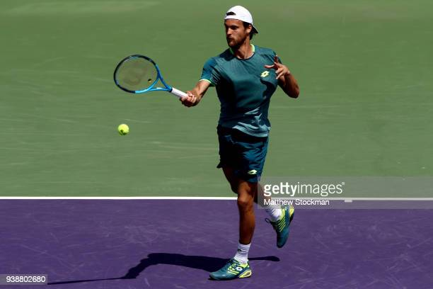 Joao Sousa of Portugal returns a shot against Hyeon Chung of Korea during the Miami Open Presented by Itau at Crandon Park Tennis Center on March 27...