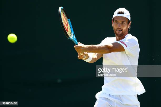 Joao Sousa of Portugal returns to Sergiy Stakhovsky of Ukraine during their Men's Singles first round match on day one of the Wimbledon Lawn Tennis...
