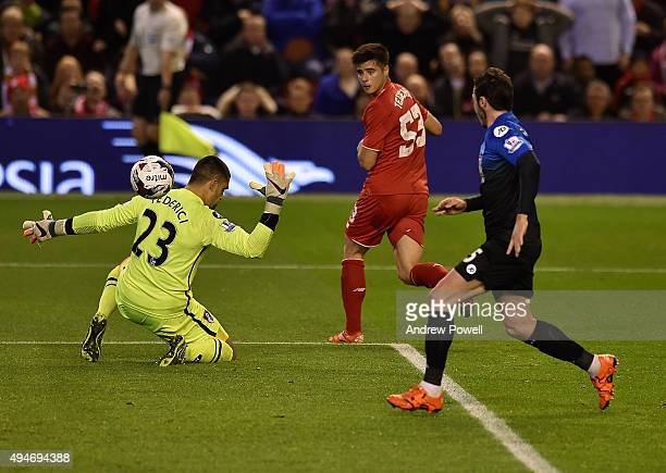 Joao Teixeira of Liverpool flicks the ball past Adam Federici of AFC Bournemouth to provide the assist for the first goal during the Capital One Cup...