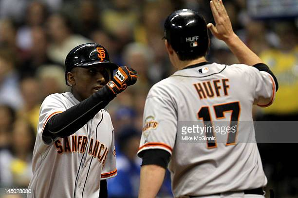 Joaquin Arias of the San Francisco Giants highfives Aubrey Huff after hitting a tworun homer in the top of the fourth inning against the Milwaukee...