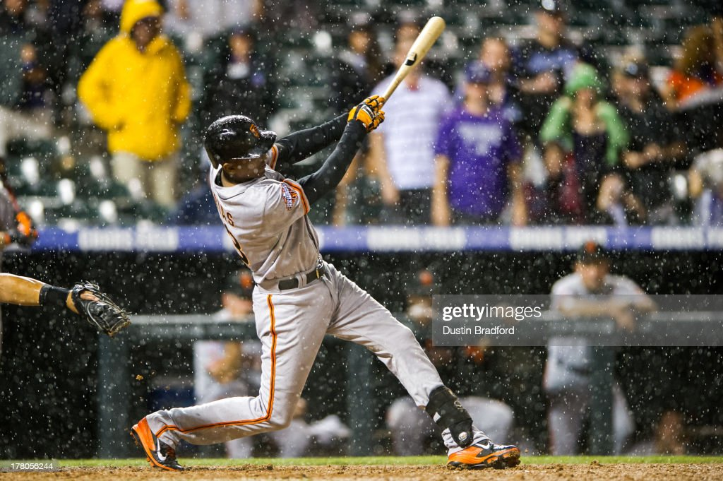 Joaquin Arias #13 of the San Francisco Giants hits a ninth inning RBI double as rain falls during a game against the Colorado Rockies at Coors Field on August 26, 2013 in Denver, Colorado. The Rockies beat the Giants 6-1.