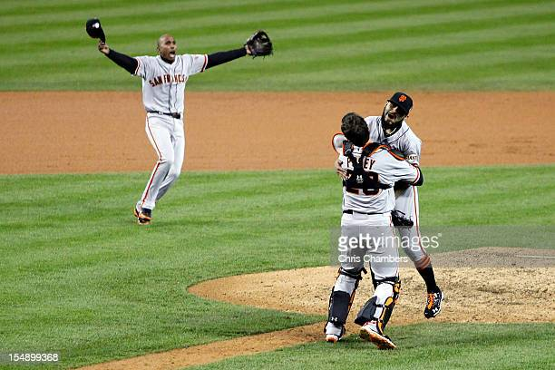 Joaquin Arias of the San Francisco Giants runs to Sergio Romo of the San Francisco Giants as he hugs Buster Posey after striking out Miguel Cabrera...