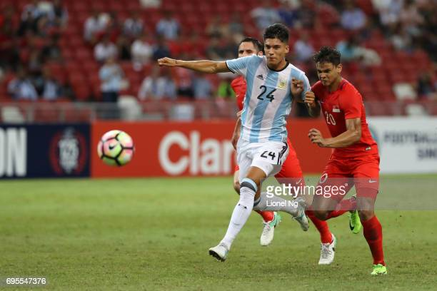 Joaquin Correa of Argentina is held by Muhammad Safuwan Bin Baharudin of Singapore during the international friendly match between Argentina and...