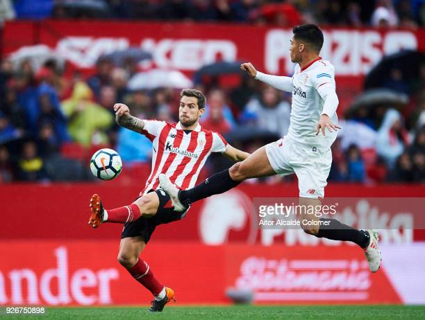 Joaquin Correa of Sevilla CF duels for the ball with Inigo Martinez of Athletic Club during the La Liga match between Sevilla CF and Athletic Club at...