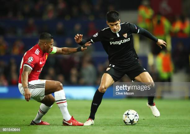 Joaquin Correa of Sevilla is watched by Antonio Valencia of Manchester United during the UEFA Champions League Round of 16 Second Leg match between...