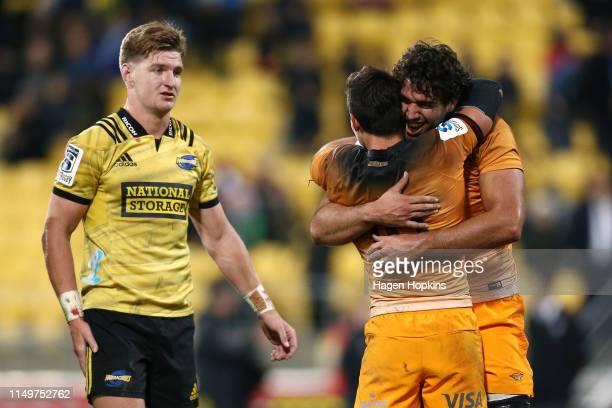 Joaquin Diaz Bonilla and Lucas Paulos of the Jaguares celebrate the win while Jordie Barrett of the Hurricanes looks on during the round 14 Super...