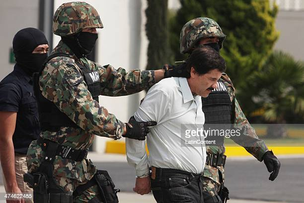 Joaquin 'El Chapo' Guzman is escorted to a helicopter in handcuffs by Mexican navy marines at a navy hanger Guzman leader of Mexico's Sinaloa drug...