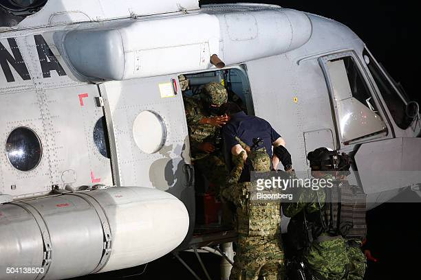 Joaquin Guzman, the world's most wanted-drug trafficker, blue shirt, is escorted by Mexican security forces into a helicopter at a Navy hangar in...