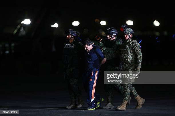 Joaquin Guzman, the world's most wanted-drug trafficker, center, is escorted by Mexican security forces at a Navy hangar in Mexico City, Mexico, on...