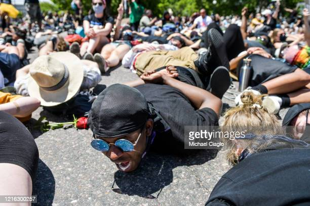 "Joaquin Hollinshed yells, ""I can't breathe,"" while joining thousands of people as they stage a die-in next to the Colorado State Capitol with their..."