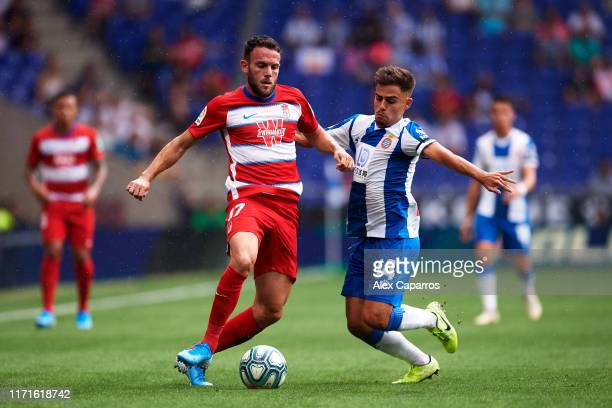 Joaquin Jose Marin 'Quini' of Granada CF battles for possession with Oscar Melendo of RCD Espanyol during the Liga match between RCD Espanyol and...