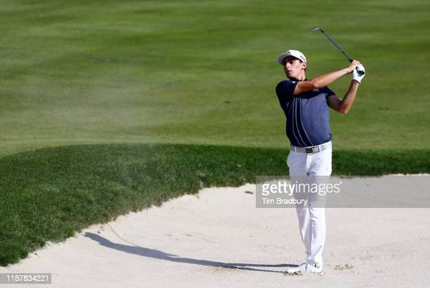 Joaquin Niemann of Chile plays a shot from a bunker on the 18th hole during the final round of the Travelers Championship at TPC River Highlands on...