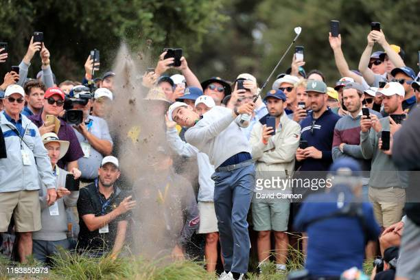 Joaquin Niemann of the International Team plays his second shot on the 18th hole in his match with Byeong Hun An against Matt Kuchar and Tony Finau...
