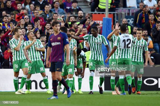 Joaquin of Real Betis celebrates after scoring his team's second goal as Lionel Messi of Barcelona looks dejected during the La Liga match between FC...