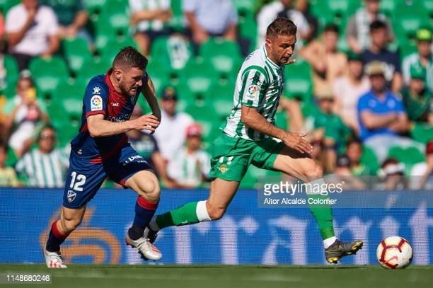 Joaquin Sanchez of Real Betis Balompie being followed by Javi Galan of SD Huesca during the La Liga match between Real Betis Balompie and SD Huesca...