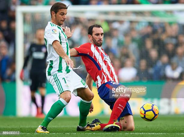 Joaquin Sanchez of Real Betis Balompie competes for the ball with Diego Godin of Club Atletico de Madrid during the La Liga match between Real Betis...