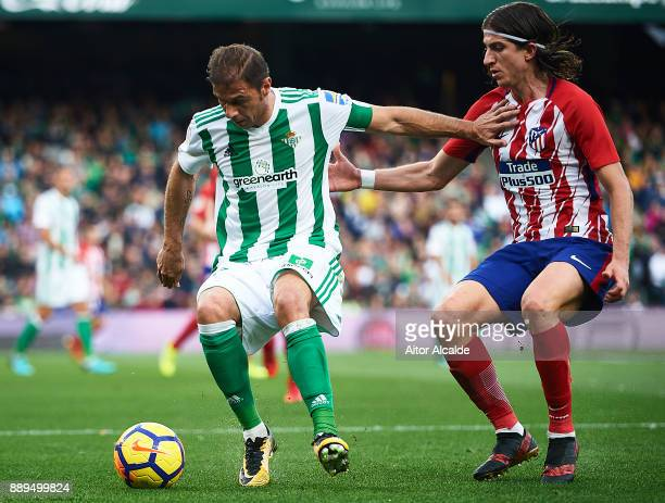 Joaquin Sanchez of Real Betis Balompie competes for the ball with Filipe Luis of Club Atletico de Madrid during the La Liga match between Real Betis...