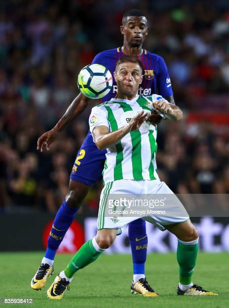 Joaquin Sanchez of Real Betis Balompie wins the header after Nelson Semedo of FC Barcelona during the La Liga match between FC Barcelona and Real...