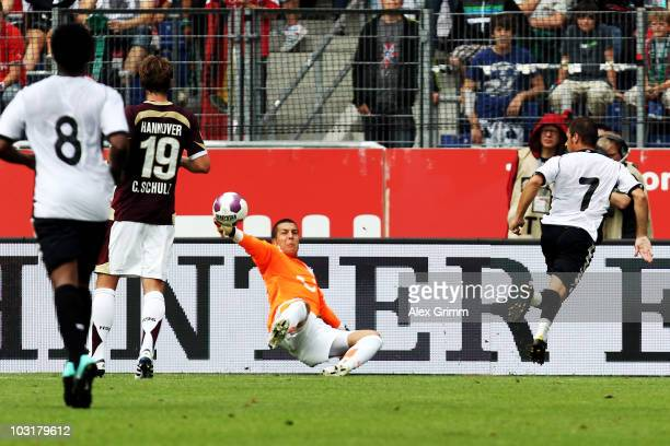 Joaquin Sanchez Rodriguez of Valencia scores his team's second goal against goalkeeper Florian Fromlowitz of Hannover during the preseason friendly...