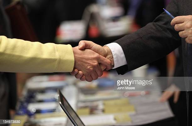 A job applicant and a potential employer shake hands at the 'Denver Hires Job Fair' on December 5 2011 in Denver Colorado Last week the US government...