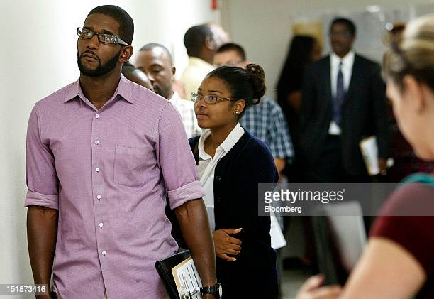 Job applicants Tyrone Smith and Monika Fogar wait in line for an interview during a hiring fair for the renovated West Los Angeles Orchard Supply...