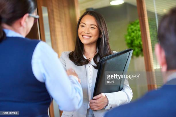 job candidate smiling as she enters the interview - job search stock pictures, royalty-free photos & images