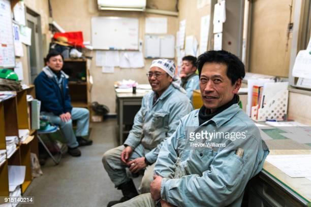 Job foremen taking a break in a shipbuilding factory office