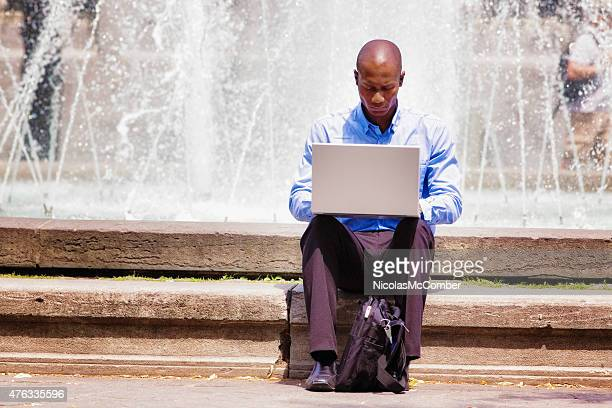 Job hunter using laptop outdoors with bag betweeen his legs