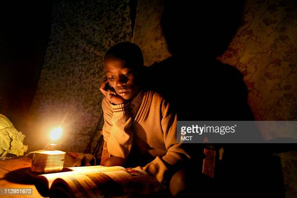 Job Onyando does his homework by the light of a parafin candle in his one room home that is nearly pitch black save for the light that comes through...