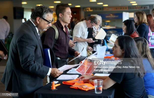Job seeker and Navy veteran David Cruz of San Jose left speaks with a Caltrans recruiter during a career fair held at ATT Park in San Francisco Calif...