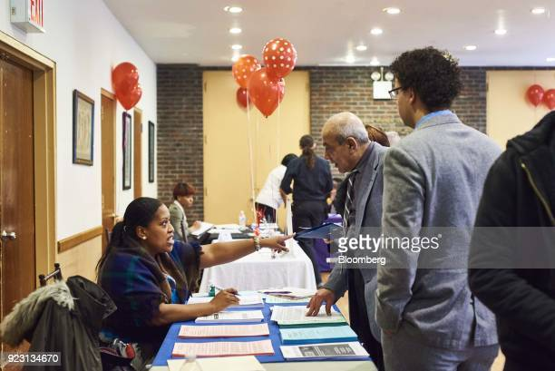 A job seeker center speaks with a representative during a Shades of Commerce Career Fair in the Brooklyn borough of New York US on Saturday Feb 17...