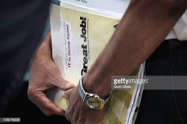 Job seeker clutches a catalogue for a job-training program collected at a job fair hosted by Illinois State Senator Dan Kotowski and the Illinois...