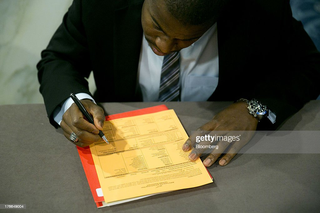 Job seeker Emmitt Candler fills out a registration card to enter the Black Data Processing Associates (BDPA) career fair in Washington, D.C., U.S., on Friday, Aug. 16, 2013. The U.S. Department of Labor is scheduled to release initial jobless claims on Aug. 22. Photographer: Andrew Harrer/Bloomberg via Getty Images