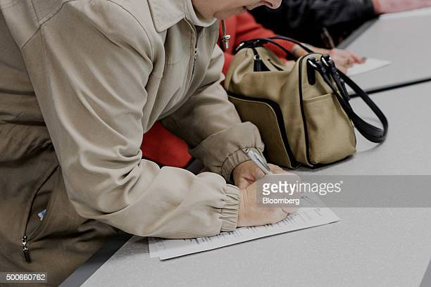 A job seeker fills out an application form during a United States Postal Service recruitment event in Boston Massachusetts US on Wednesday Dec 9 2015...