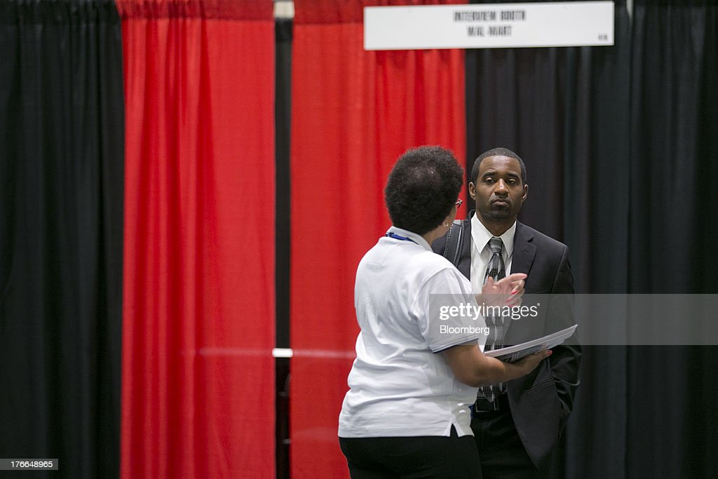Job seeker Freddy Lyons II talks to a job recruiter at the Black Data Processing Associates (BDPA) career fair in Washington, D.C., U.S., on Friday, Aug. 16, 2013. The U.S. Department of Labor is scheduled to release initial jobless claims on Aug. 22. Photographer: Andrew Harrer/Bloomberg via Getty Images