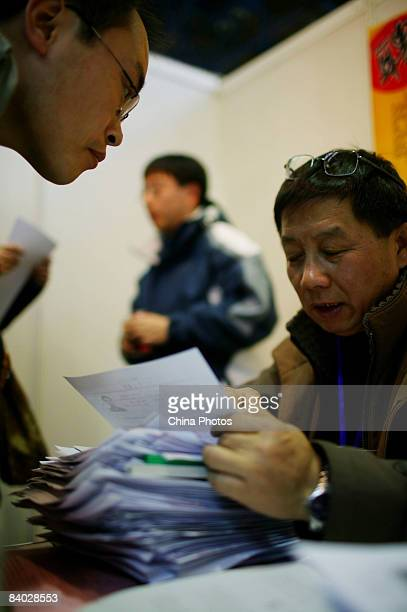 A job seeker hands in his resume at a job fair for postgraduate students on December 14 2008 in Beijing China Nearly 40000 applicants competed for...