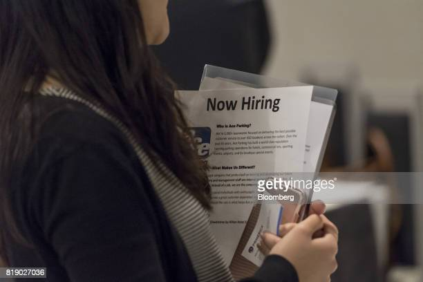 A job seeker holds a Now Hiring information sheet while talking to a recruiter during a CoasttoCoast career fair in San Jose California US on...