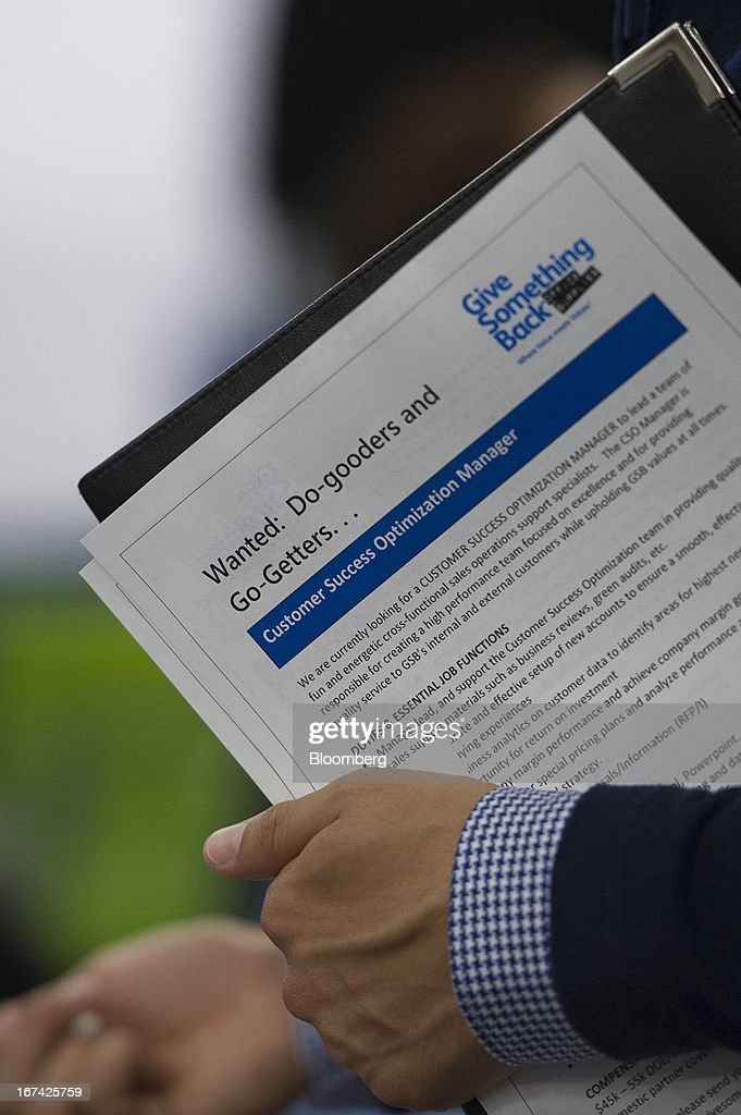 A job seeker holds paperwork while talking with a recruiter at the Spring LGBT Career Fair in San Francisco, California, U.S., on Wednesday, April 24, 2013. Fewer Americans than forecast filed first-time claims for unemployment insurance payments last week, pointing to an improving labor market. Photographer: David Paul Morris/Bloomberg via Getty Images