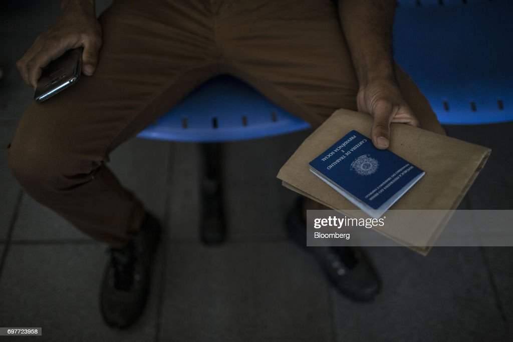 A job seeker holds work documents inside the Ministry of Labor and Employment building in Rio de Janeiro, Brazil, on Monday, June 19, 2017. The Brazil Labor Ministry is scheduled to release government registered job creation figures on June 20. Photographer: Dado Galdieri/Bloomberg via Getty Images