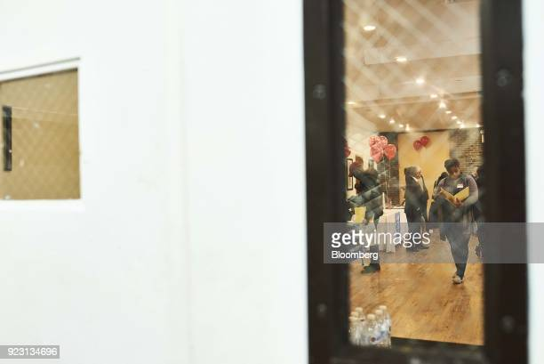A job seeker is seen reviewing paperwork through a window during a Shades of Commerce Career Fair in the Brooklyn borough of New York US on Saturday...