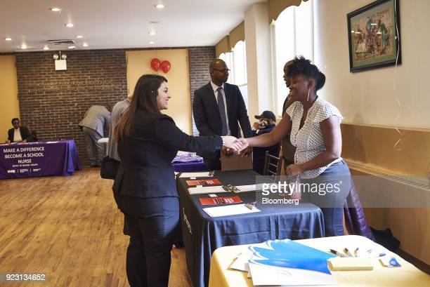 A job seeker left shakes hands with a representative during a Shades of Commerce Career Fair in the Brooklyn borough of New York US on Saturday Feb...
