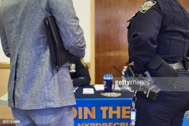 A job seeker left speaks with a New York Police Department officer during a Shades of Commerce Career Fair in the Brooklyn borough of New York US on...