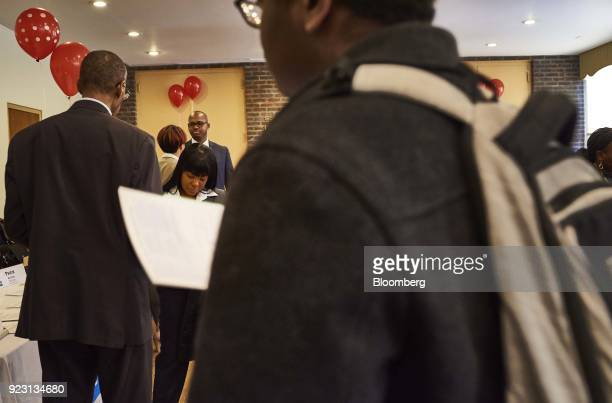 A job seeker left speaks with a representative center during a Shades of Commerce Career Fair in the Brooklyn borough of New York US on Saturday Feb...