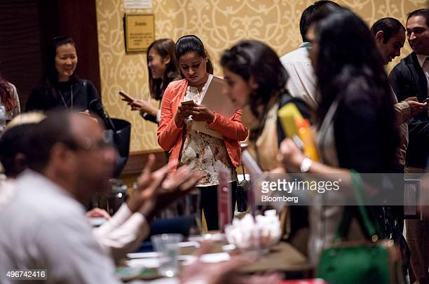 A job seeker looks at her smartphone as she waits to meet with recruiters during the San Jose Career Fair in San Jose California US on Tuesday Nov 10...