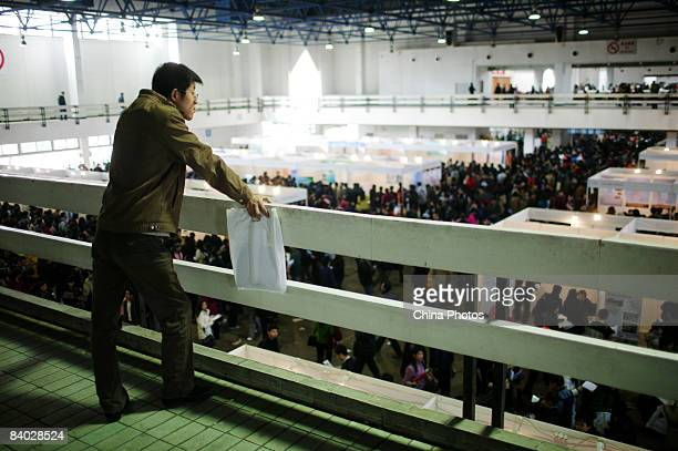 A job seeker overlooks crowd ats at a job fair for postgraduate students on December 14 2008 in Beijing China Nearly 40000 applicants competed for...
