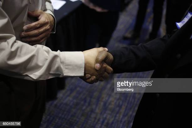 A job seeker right shakes hands with a recruiter during a Job News USA career fair in Overland Park Kansas US on Wednesday March 8 2017 Applications...