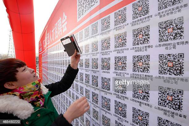 A job seeker scans QR codes during the 2nd Shanxi Exhibition Hall Job Fair on March 6 2015 in Taiyuan Shanxi province of China A new mode of 'Offline...
