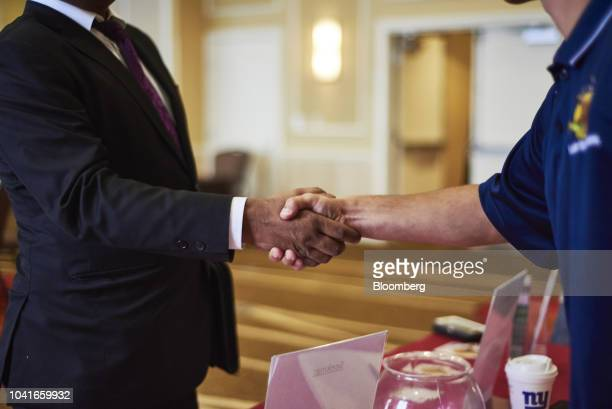 A job seeker shakes hands with a representative during a National Career Fair event in Edison New Jersey US on Thursday Sept 20 2018 Filings for US...