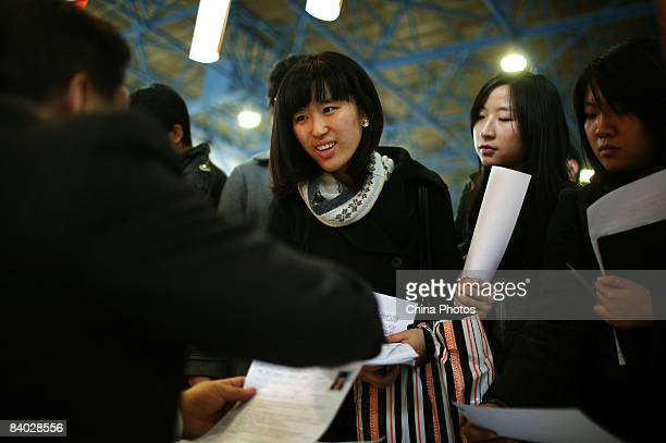 Job seekers hand in their resumes at a job fair for postgraduate students on December 14 2008 in Beijing China Nearly 40000 applicants competed for...